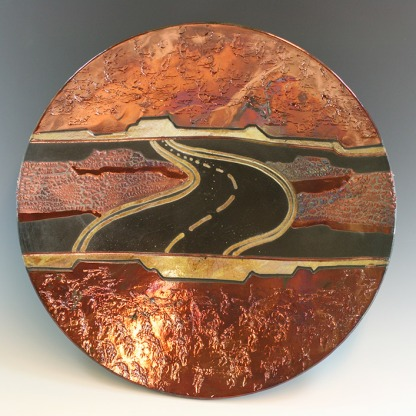 Raku-wall-plate-textured-with-carved-road,-copper